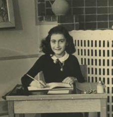 Anne Frank sitting at school desk.