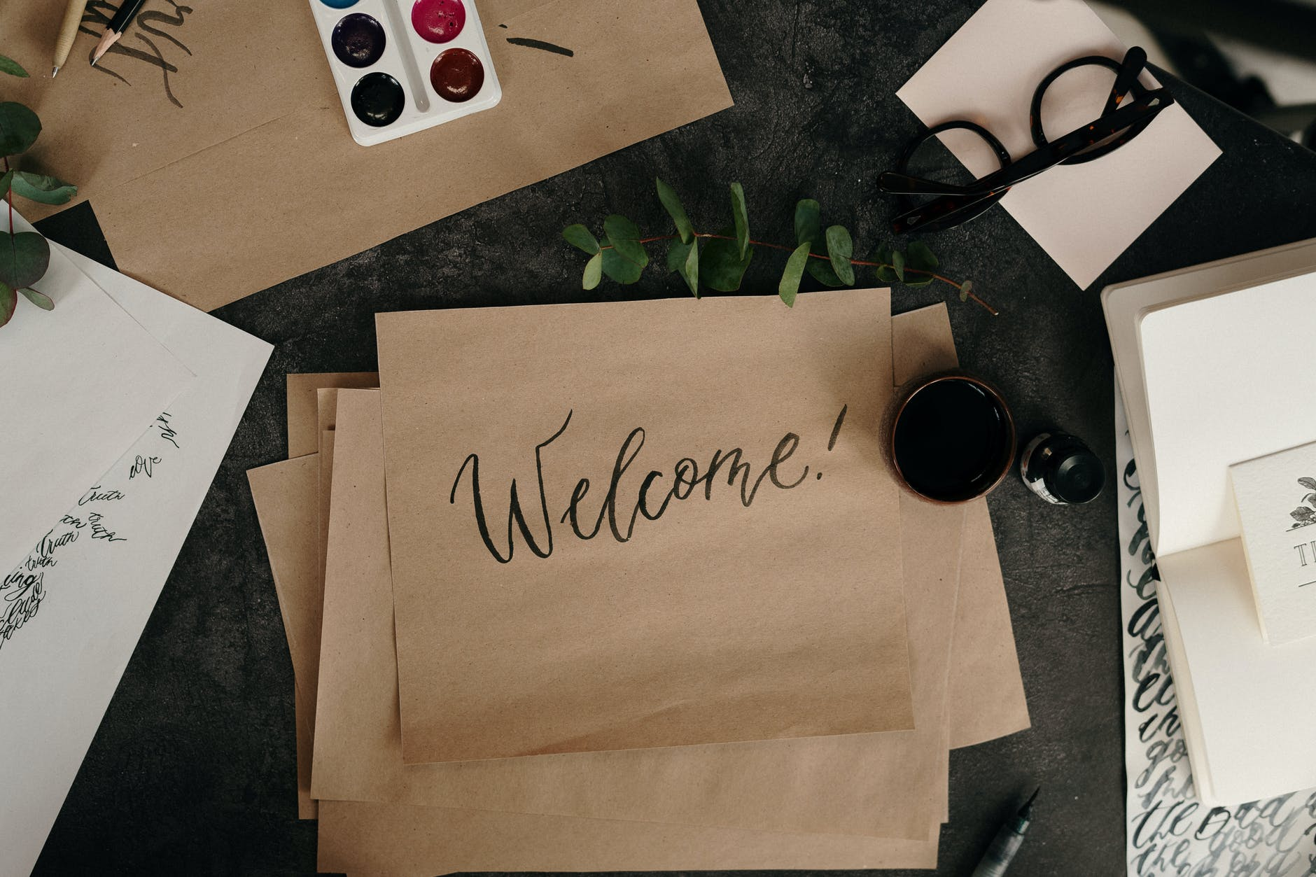 """A photo of a cluttered desk with a sheet of paper with """"Welcome!"""" written on it."""